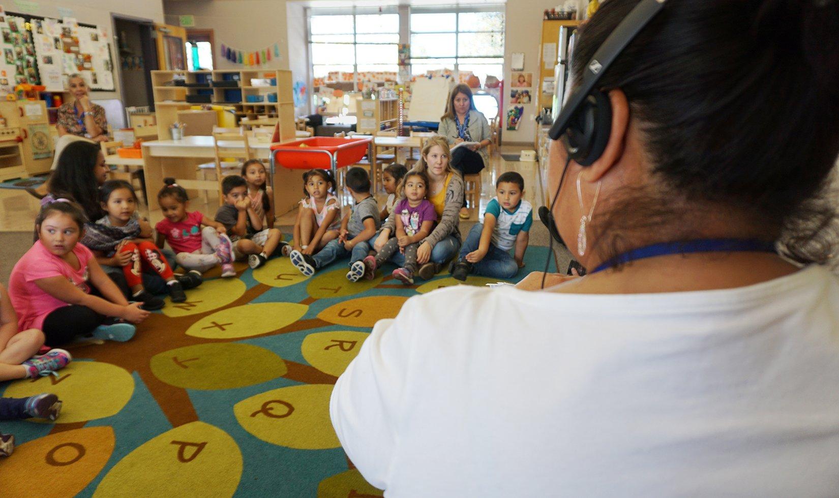 a preschool teacher addressing a class of students using her TALLK headset donated by the John Jordan Foundation