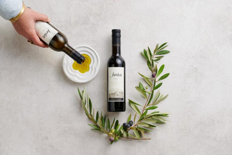 Bottles of Jordan Estate Extra Virgin Olive Oil and a olive branch